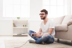 Gelukkige jonge mens die thuis videospelletjes spelen royalty-vrije stock afbeeldingen