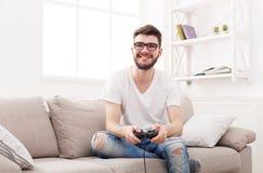 Gelukkige jonge mens die thuis videospelletjes spelen stock foto's