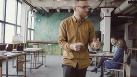Gelukkige jonge mens die in vrolijke stemming door het gekke bureau en dansen lopen De zakenman begroet met collega's stock footage