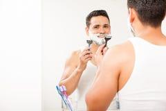 Gelukkige jonge mens die zijn baard scheren stock foto's