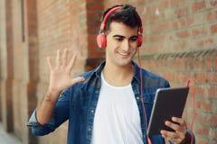 Gelukkige jonge mens die zijn tablet gebruiken stock afbeelding