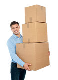 Gelukkige jonge mens die zware pakketten draagt Royalty-vrije Stock Fotografie