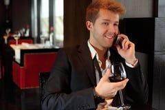 Gelukkige mens in kostuum bij restaurant die op de telefoon spreken stock foto's