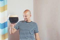 Gelukkige, jonge mens met een zeer grote mok bier Hij lacht en verheugt zich, en toen dranken stock afbeelding