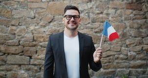 Gelukkige jonge mens nationale vlag van Frankrijk houden die zich bevindt in openlucht glimlachend stock video