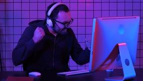Gelukkige jonge mens in oogglazen met hoofdtelefoon speel en winnend computerspel royalty-vrije stock afbeeldingen