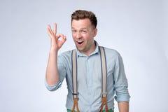Gelukkige jonge mens in overhemd en bretels die O.K. teken gesturing stock afbeeldingen