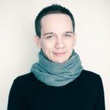 Gelukkige jonge mens in zwarte sweater en grijze sjaal Royalty-vrije Stock Fotografie