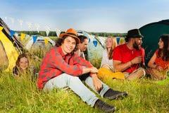 Gelukkige jonge mensenzitting op gras bij het kamperen Royalty-vrije Stock Afbeeldingen