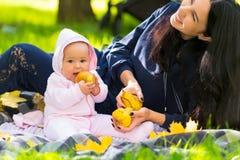 Gelukkige jonge moeder die bij haar babymeisje lachen stock afbeeldingen