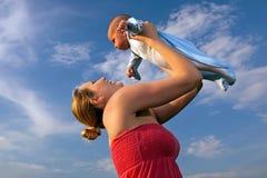 Gelukkige jonge moeder die haar hoogte van de babyjongen opheft Royalty-vrije Stock Fotografie