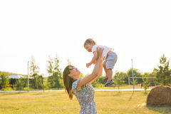 Gelukkige jonge moeder die met haar weinig babyzoon op de zonneschijn warme herfst of de zomerdag spelen Mooi zonsonderganglicht  royalty-vrije stock foto's