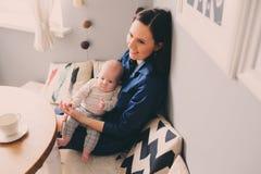 Gelukkige jonge moeder die ontbijt in moderne keuken met haar babydochter hebben Stock Foto