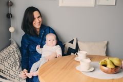 Gelukkige jonge moeder die ontbijt in moderne keuken met haar babydochter hebben Royalty-vrije Stock Afbeeldingen