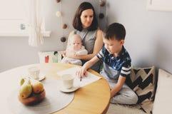 Gelukkige jonge moeder die ontbijt in moderne keuken met haar van het babydochter en jonge geitje zoon hebben royalty-vrije stock fotografie