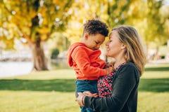 Gelukkige jonge moeder die zoete peuterjongen houden Royalty-vrije Stock Afbeeldingen
