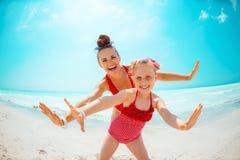 Gelukkige jonge moeder en dochter op zeekust die prettijd hebben royalty-vrije stock afbeeldingen