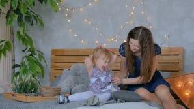 Gelukkige jonge moeder en haar babydochter die togerher spelen stock videobeelden
