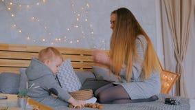Gelukkige jonge moeder en haar babyzoon die met okkernoten spelen stock videobeelden