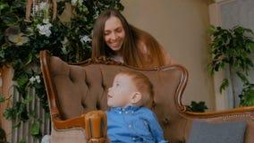Gelukkige jonge moeder en haar babyzoon die togerher spelen stock footage