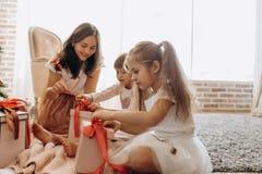 Gelukkige jonge moeder en haar twee charmante dochters in aardige dresse royalty-vrije stock afbeeldingen