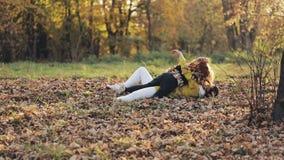 Gelukkige jonge moeder en haar weinig roodharigedochter die Pret in een de herfstpark hebben , En zij die koesteren lachen spelen stock video