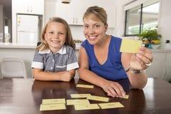 Gelukkige jonge moeder en haar zoet en mooi weinig het spel thuis keuken die van de dochterspeelkaart en pret samen glimlachen he stock fotografie