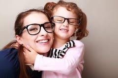 Gelukkige jonge moeder en lauging jong geitje Stock Fotografie