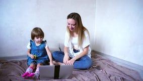 Gelukkige jonge moeder en weinig dochter die samen bij computer spelen spelen, die op vloer in heldere dagruimte zitten stock video