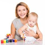Gelukkige jonge moeder met een babyverf door handen Stock Afbeeldingen