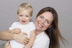 Gelukkige jonge moeder met een kind op lichtgrijze achtergrond Stock Fotografie