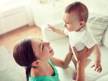Gelukkige jonge moeder met weinig baby thuis stock foto