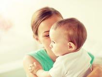 Gelukkige jonge moeder met weinig baby thuis royalty-vrije stock foto's