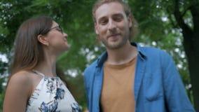 Gelukkige jonge moeder met weinig dochter bekijken en vader die in openlucht koesteren stock video