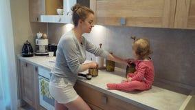 Gelukkige jonge moederkoks met een kind dat op een lijst thuis keuken zit stock video