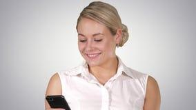 Gelukkige jonge mooie vrouw die en mobiele telefoon, Alpha Channel glimlachen met behulp van stock video
