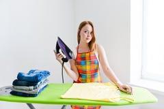Gelukkige jonge mooie vrouw het strijken kleren. Stock Foto's