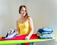 Gelukkige jonge mooie vrouw het strijken kleren. Stock Foto
