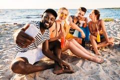 gelukkige jonge multi-etnische vrienden die selfie met smartphone nemen terwijl samen het doorbrengen van tijd stock foto