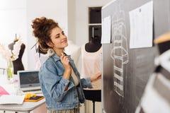 Gelukkige jonge ontwerper die de schets en voelen tevreden met het bekijken stock fotografie