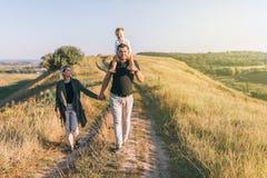 gelukkige jonge ouders die handen houden terwijl vader aanbiddelijk dragen weinig zoon stock foto's