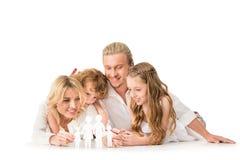 gelukkige jonge ouders en jonge geitjes met document familiemodel stock fotografie