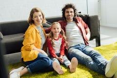 gelukkige jonge ouders met leuk weinig dochterzitting samen bij tapijt en het glimlachen stock fotografie