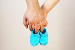 Gelukkige jonge oudersgreep in hun schoenen van de handenbaby van toekomstige chi Stock Foto