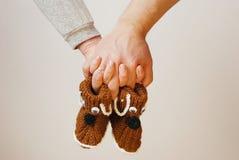 Gelukkige jonge oudersgreep in hun schoenen van de handenbaby van toekomstige chi Stock Afbeeldingen