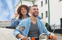 Gelukkige jonge paar berijdende autoped in stad Knappe kerel en jonge vrouwenreis Avontuur en vakantiesconcept royalty-vrije stock foto's