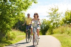 Gelukkige jonge paar berijdende fietsen in de zomer stock foto