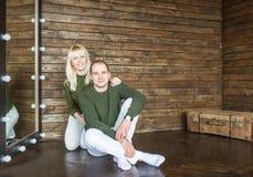 Gelukkige jonge paar het glimlachen zitting op houten vloer thuis Royalty-vrije Stock Afbeelding