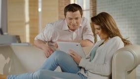 Gelukkige jonge paar het letten op familiefoto's op tabletpc, geheugen stock footage