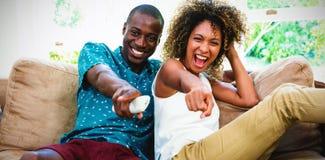 Gelukkige jonge paar het letten op televisie stock foto
